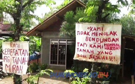 Poster berisi protes warga atas ganti rugi proyek Bendung Bener.