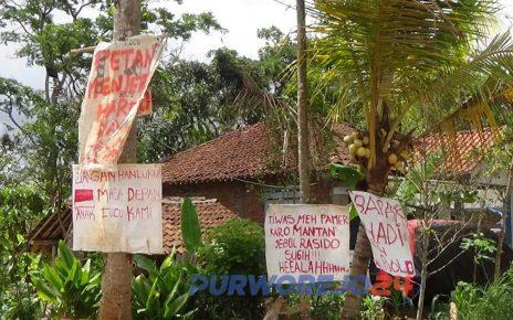 Warga memasang poster di sepanajang dalan desa untuik protes ganti-rugi proyek Bendung Bener. (12/12/2019)