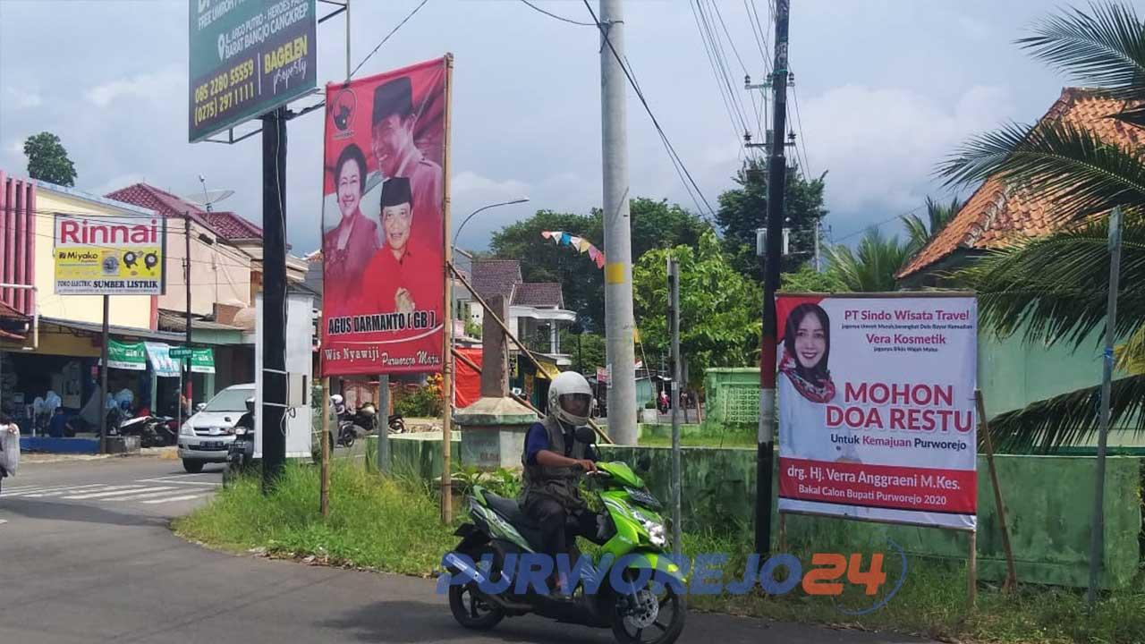 Pengendara motor melintas di depan baliho dan poster bergambar bakal calon bupati-wakil bupati Purworejo
