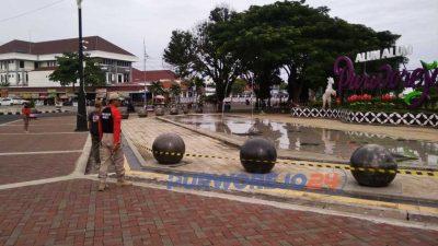 Satpol PP memasang pita kuning sebagai penanda larangan melitnas di sejumlah fasilitas umum di Alun-alun Purworejo