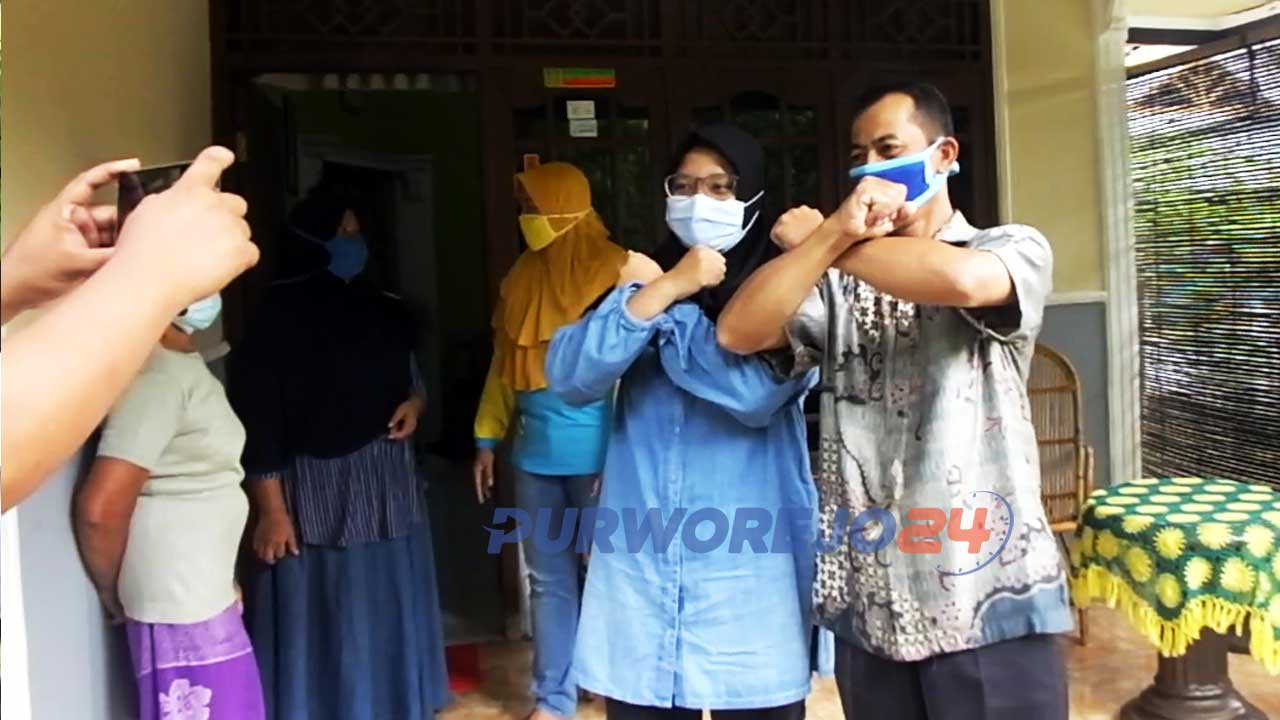 Dwi Rahayu, perawat yang sembuh dari positif Covid-19 berfoto bersama warga saat penyambutan kepulangan dari Rumah Sakit.