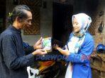 Koordinator Baksos Cholifatun Jannah menyerahkan bantuan ke Haryanto Dje, seniman yang terdampak ekonomi pandemi korona.