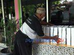 Perangkat Desa Krandegan merapikan makanan yang ada di Meja Anti Lapar