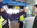Petugas melakukan pengecekan suhu badan penumpang KA.