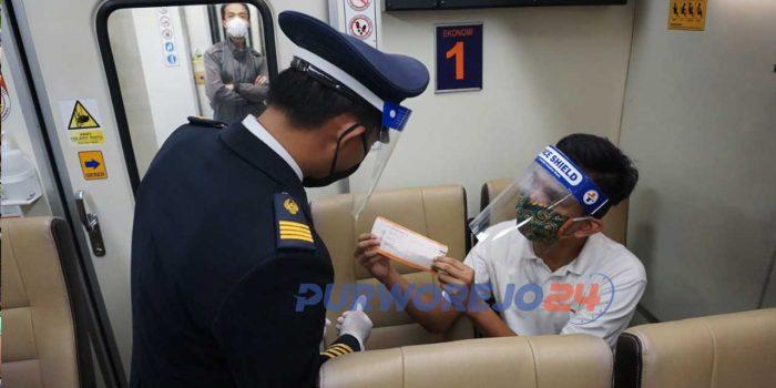 Seorang penumpang memperlihatkan tiket kepada petugas