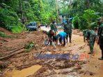 Warga bersama anggota TNI membersihkan material longsor yang menutup jalan.