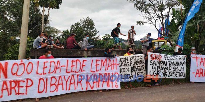 Puluhan warga membentangkan spanduk di jalan masuk proyek Bendungan Bener di Dusun Kalipancer.