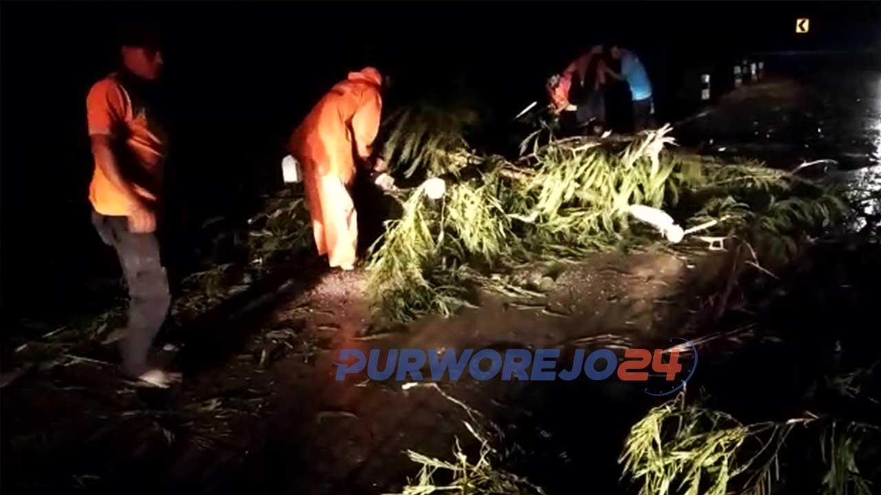 Warga dibantu relawan dan petugas BPBD membersihkan batang pohon tumbang.