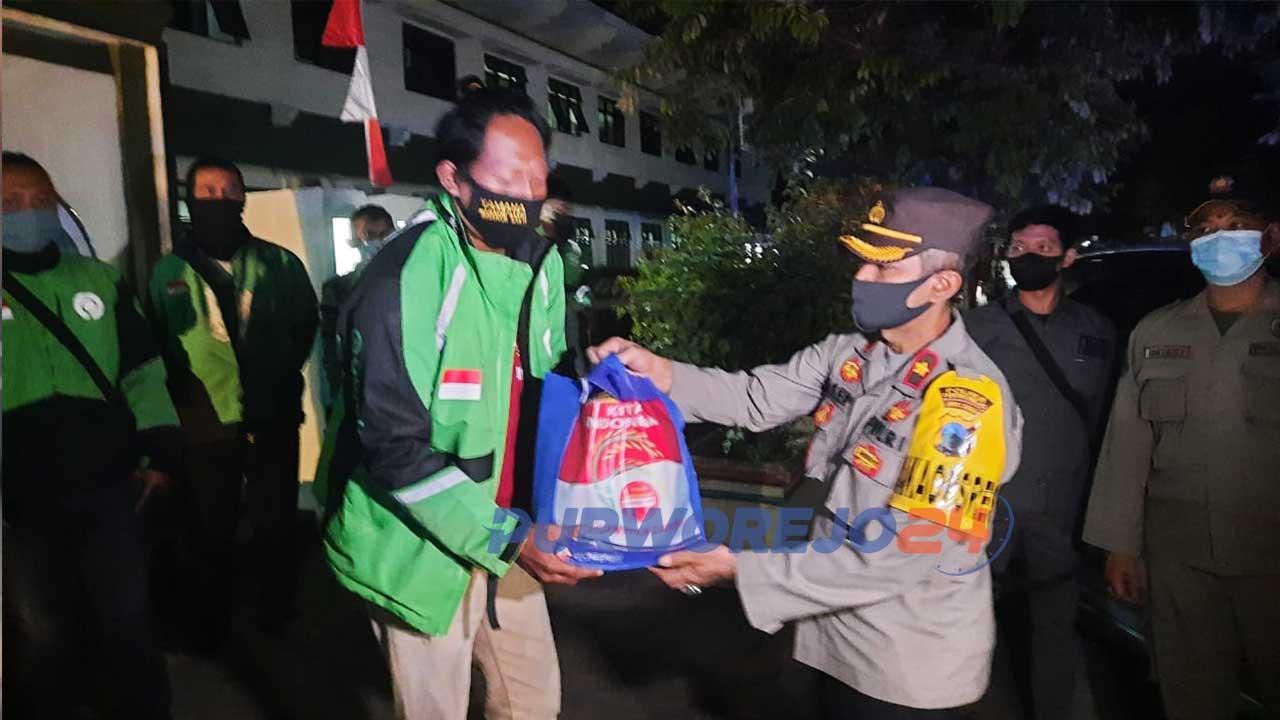 Kapolres Purworejo menyerahkan paket sembako kepada pengojek daring.